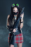 Brunette girl with dreadlocks and with a gun in his hand