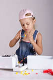 Girl tighten screws to screw wrench, repairing toy
