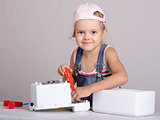 Girl repairs screwdriver toy microwave