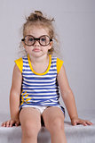 Two-year-old girl funny glasses sitting looking in frame