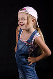 Portrait laughing four-year girl in overalls and cap