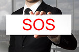 businessman holding sign sos