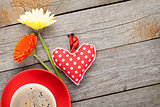 Cup of coffee, heart toy and gerbera flowers on wooden table