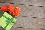 Orange gerbera flowers and gift box