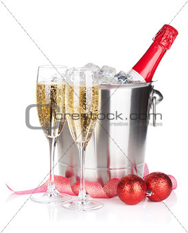 Champagne bottle in ice bucket, two glasses and christmas decor