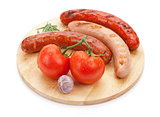 Various grilled sausages with condiments and tomatoes
