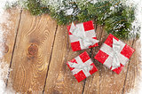 Old wood texture with snow, gift boxes and firtree