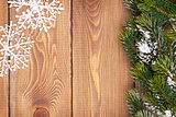 Christmas fir tree with snow and snowflake decor on rustic woode