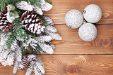 Christmas fir tree with snow and baubles on rustic wooden board