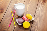 Colorful macaron cookies and cup of milk