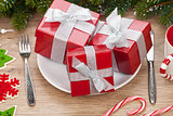 Gift boxes on plate, fir tree and christmas decor