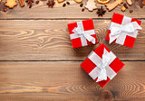 Gift boxes over christmas wooden background with spices and ging