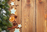 Christmas wooden background with snow fir tree, spices and ginge