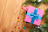 Christmas background with snow fir tree, gift box and candies