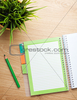 Office table with notepad, pencil and flower