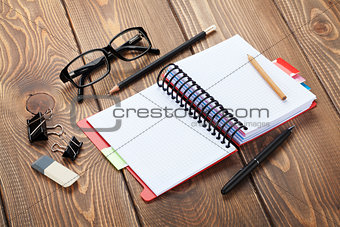 Office table with notepad, colorful pencils and supplies