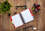 Office table with notepad, colorful pencils, supplies and flower