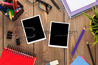 Office table with notepad, colorful pencils, supplies and photo