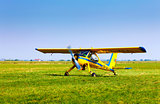 Retro yellow airplane on a green grass field preparing to take o