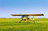 Retro yellow airplane on a green grass field preparing to take o