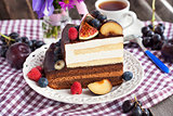 Piece of chocolate cake with cream and fresh fruit