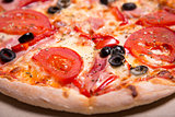 Delicious Italian pizza with ham, tomatoes and olives