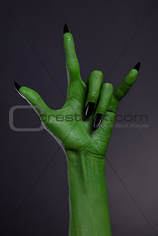 Green hand with black nails showing heavy metal gesture