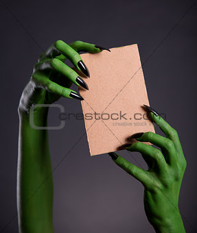 Green monster hands holding empty piece of cardboard
