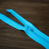 Blue zipper on dark wood background