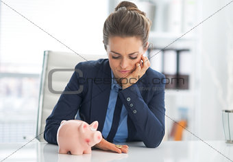 Portrait of sad business woman with piggy bank looking on coin