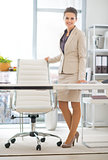 Full length portrait of happy business woman standing in office