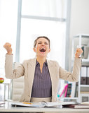 Happy business woman rejoicing in office