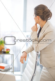 Portrait of thoughtful business woman looking in window