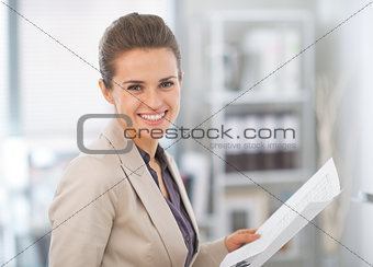 Portrait of happy business woman with documents in office