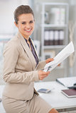 Happy business woman working with documents in office