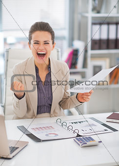 Portrait of happy business woman in office rejoicing