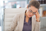 Portrait of stressed business woman with eyeglasses in office