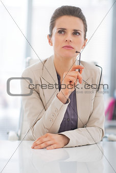 Portrait of thoughtful business woman with eyeglasses in office