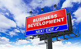 Business Development Inscription on Red Billboard.