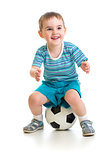 Little boy sitting on soccer ball isolated on white