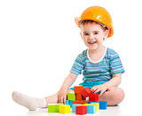kid boy in hard hat with colorful building blocks