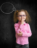 Funny child in eyeglasses standing near school chalkboard and th