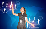 Beautiful businesswoman in dress presses virtual button. World map and business silhouettes