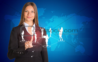 Beautiful businesswoman in suit presses finger on virtual button. World map and business silhouettes