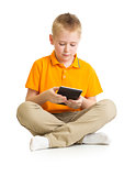 Pensive kid boy sitting with tablet pc or phablet isolated