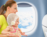 Happy mother and kid traveling together in aeroplane cabin near