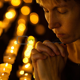 praying in Catholic church near candles. Religion concept