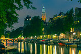 Night city view of Amsterdam canal and Westerkerk church