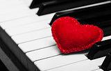 Red felt heart on piano keyboard