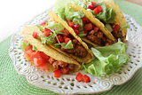Mexican food - tacos with meat, lettuce and tomatoes